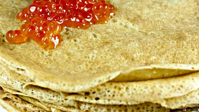 Blini are served with salmon eggs or sour cream.