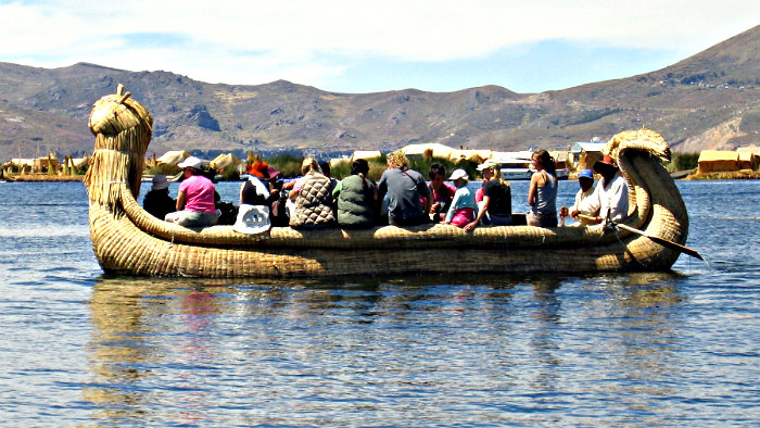Group of tourists on reed boats.