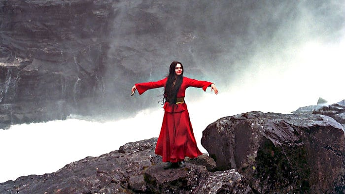 Girl in red singing Norwegian song next to the roaring waterfall.